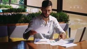 保险统计与膝上型计算机和纸一起使用在咖啡馆桌上 股票录像