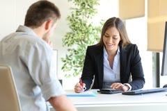 保险代理公司和顾客计算的预算 库存照片