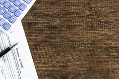 保险费税与计算器的信用在木桌上的形式和笔 库存图片