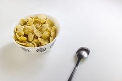 滚保龄球与与匙子的玉米片在白色背景 库存图片