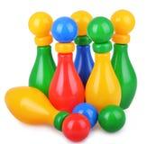 滚保龄球与五九柱游戏用的小柱和球的五颜六色的孩子 免版税库存照片