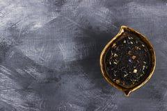 滚保龄球用与花和莓果的瓣的红茶 顶视图 免版税库存照片