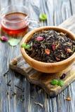 滚保龄球用与花瓣和一个杯子的红茶热的茶 图库摄影