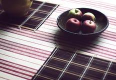 滚保龄球用在木头的苹果与镶边桌布 免版税图库摄影