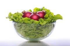滚保龄球用新鲜的沙拉和三个红色圣诞节球 图库摄影