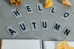 信件你好秋天和开放黄色笔记本有灰色的叶子的 库存照片