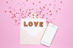 信件曲奇饼爱与信封和红心在桃红色背景 库存图片