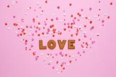 信件曲奇饼爱与桃红色和红心在桃红色背景 库存照片