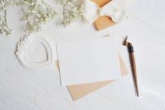 信件的嘲笑与以心脏的形式爱箱子在与麦花的一张木白色桌, V的一张贺卡上说谎 免版税库存图片