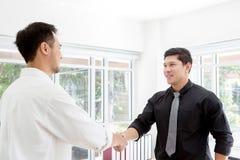 信号交换 握手的商务伙伴在办公室 握手的两个商人在办公室 库存图片