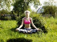 信奉瑜伽者女孩在精神成长升空的本质思考 免版税库存图片