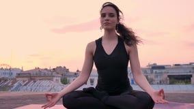 信奉瑜伽者女孩在莲花姿势在屋顶在夏天坐日落,健康生活方式,运动概念,凝思 影视素材