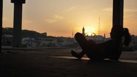 信奉瑜伽者女孩在莲花姿势坐并且改变它在被放弃的大厦在日落,健康生活方式,运动的夏天 影视素材