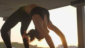 信奉瑜伽者女孩在被放弃的大厦的桥梁轮子站立在日落,健康生活方式,运动概念的夏天 股票录像