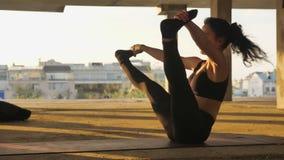 信奉瑜伽者女孩在被放弃的大厦的navasana在夏天坐日落,健康生活方式,运动概念,体育 股票录像