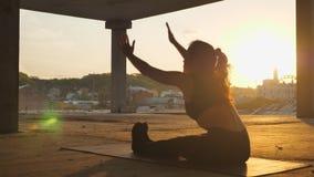 信奉瑜伽者女孩走向在被放弃的大厦的paschimottanasana在日出,健康生活方式,运动概念的夏天 股票视频