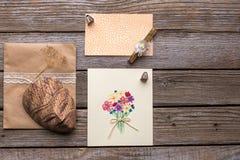 信封、明信片和面具在木背景 免版税库存图片