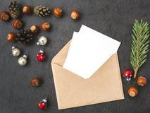 信封、锥体、榛子和圣诞节装饰 免版税库存照片