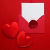 信封在红色背景的邮件、心脏和蜡封印 情人节卡片、爱或者婚礼问候概念 顶视图 免版税库存图片