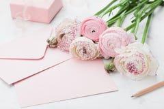 信封或信件、纸牌、礼物和桃红色毛茛属在招呼的白色桌上开花在母亲或妇女天 库存图片