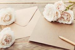 信封或信件、纸牌和葡萄酒玫瑰色花在土气木桌上招呼的在母亲或妇女天 库存照片