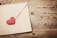 信封或信件和红色心脏在葡萄酒木桌上爱消息的在情人节在减速火箭定调子 免版税库存照片