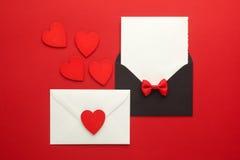 信封邮件、心脏和丝带在红色背景 情人节卡片、爱或者婚礼问候概念 顶视图 免版税库存照片
