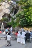 信徒在卢尔德临近洞穴 免版税图库摄影