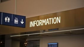 `信息在infopoint书桌的`霓虹标签和垂悬洗手间和推力图表在机场大厅 免版税图库摄影