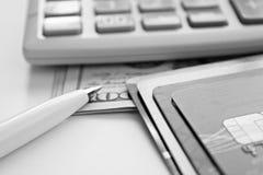 信用卡、计算器、笔和美国美元兑现在办公桌桌上的金钱 库存图片