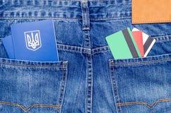 信用卡和两本蓝色乌克兰护照在蓝色牛仔裤的口袋 免版税库存照片