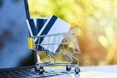信用卡和使用膝上型计算机分期付款网络购物有信用的概念手推车和借记卡在网上购物的 免版税库存照片