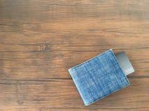 信用卡在棕色木桌上的蓝色牛仔裤钱包里 库存照片