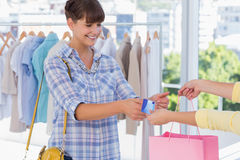 给信用卡的出纳员一名微笑的顾客 免版税库存图片