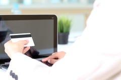 信用卡的年轻女商人输入的数据 在网上 免版税库存照片