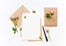 信件、信封和礼物在白色背景 邀请卡片或者情书与桃红色玫瑰 假日概念,顶视图,平的l 免版税库存图片