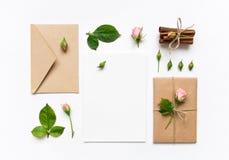 信件、信封和礼物在白色背景 邀请卡片或者情书与桃红色玫瑰 假日概念,顶视图,平的l 库存照片