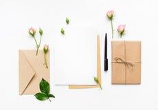 信件、信封和礼物在白色背景 邀请卡片或者情书与桃红色玫瑰 假日概念,顶视图,平的l 图库摄影