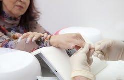 修剪在女性现有量法式修剪的进程,做钉子扩展名 免版税库存图片