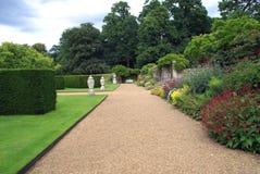 修剪的花园有装饰品、长凳和草本边界的庭院道路 免版税库存照片