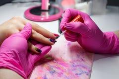 修剪钉子油漆,特写镜头被射击接受修指甲的钉子沙龙的一名妇女由美容师 免版税库存照片
