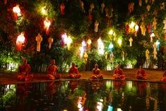 修士在五颜六色的纸灯中的池塘旁边思考我 图库摄影