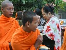修士是在Sangkhl提供他们食物的走的通行证人民 免版税库存图片