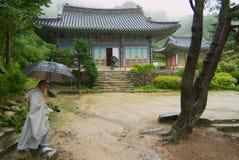 修士由Jeondeungsa寺庙疆土走在一个雨天在茵契隆,韩国 免版税图库摄影