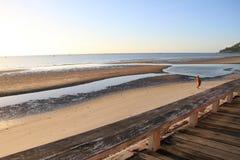 修士走在海滩的,日出 免版税库存照片