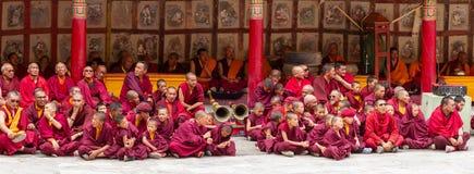 修士,礼节鼓手,有乐器的号手作为西藏佛教可汗舞蹈节日的观众在Hemis 免版税库存图片