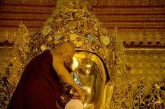 修士洗面孔并且刷菩萨图象的牙在玛哈Myat自治都市 免版税库存图片