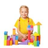 修建从颜色玩具块的愉快的小女孩房子。 库存图片