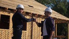 ?? 修建建筑师慢动作录影的概念大厦 建造者在盔甲握手的两个人收缩 影视素材