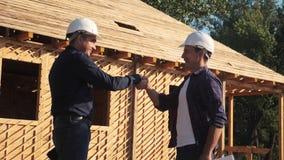 ?? 修建建筑师慢动作录影的概念大厦 建造者在盔甲握手的两个人收缩 股票录像